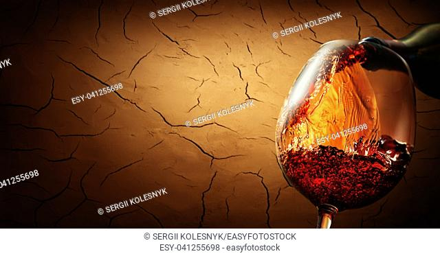 Wine pouring from bottle into wineglass on cracked clay background