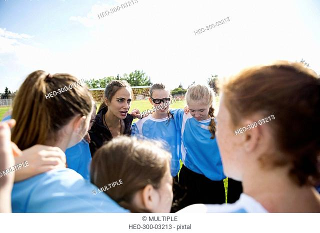 Middle school girl soccer team and coach huddling on field
