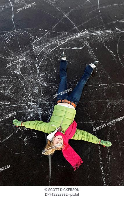 A Young Woman Lays On Her Back On A Frozen Surface Looking Up While Ice Skating; Alaska, United States Of America