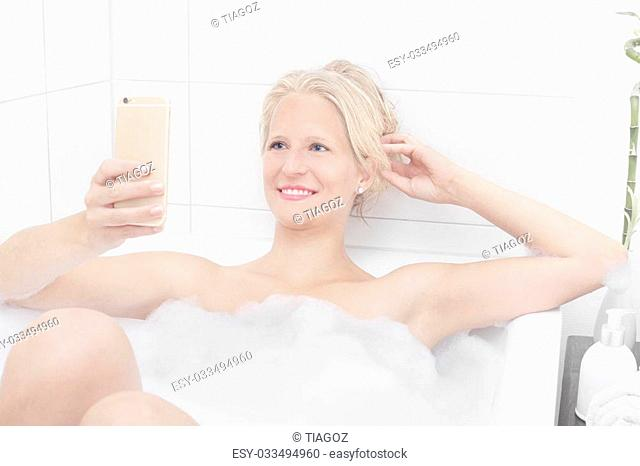 blonde beautiful woman taking a bath with bubbles looking at her phone