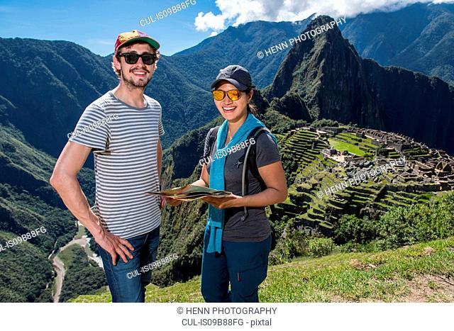 Couple at Inca ruins looking at camera smiling, Machu Picchu, Cusco, Peru, South America