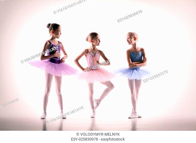 The silhouettes of little ballerinas in dance studio posing on a white background