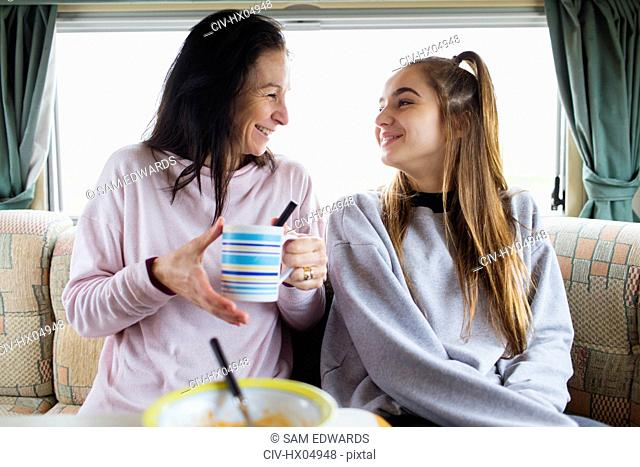 Happy mother and daughter enjoying hot chocolate in motor home