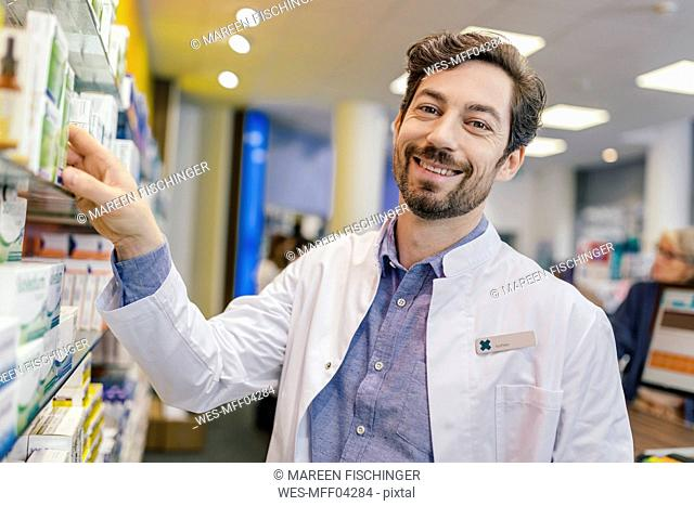 Portrait of smiling pharmacist with medicine at shelf in pharmacy