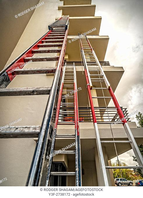 Tall painters ladders lean against an apartment block being painted. Cape Town, South Africa