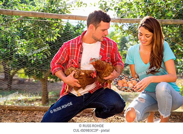 Organic farming couple holding free range chicken and basket of eggs