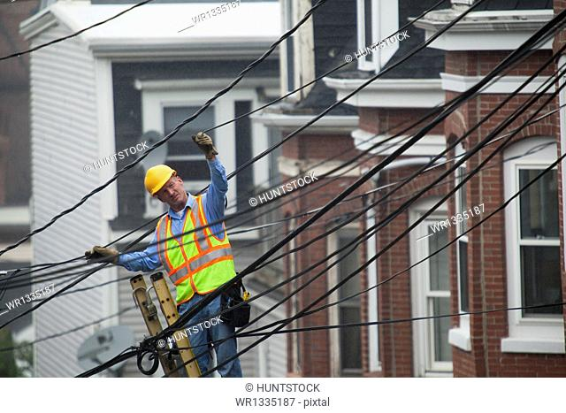 Cable lineman stretching a cable in the city from ladder