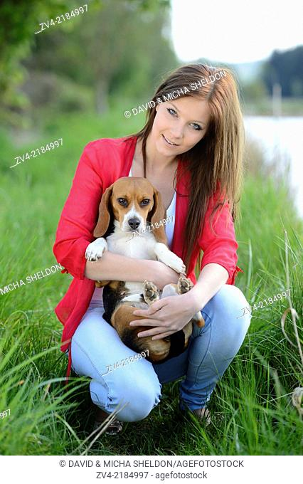 Close-up of a young woman with her Beagle dog in spring