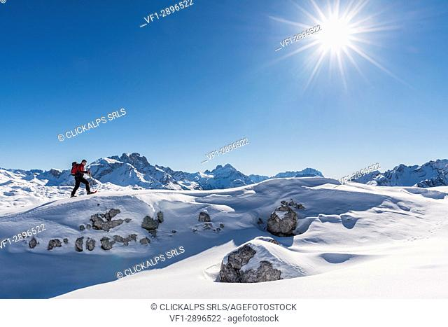 San Vigilio di Marebbe, Sennes, Dolomites, Bolzano province, South Tyrol, Italy. A view of a hiker going up a hill with snowshoes