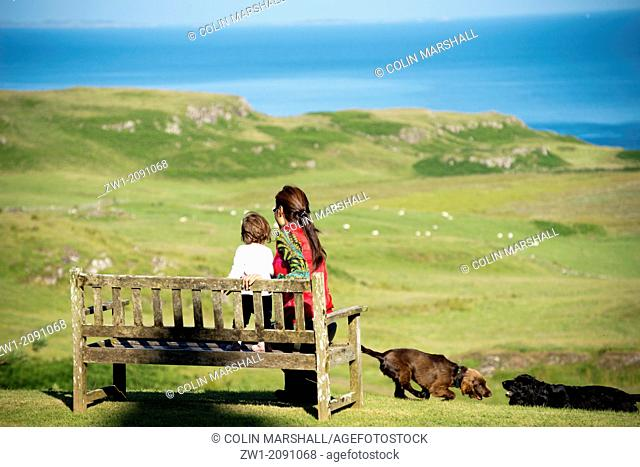 Mother and child (both model released) on bench with dogs looking out to sea from Glengorm Castle, near Tobermory, Isle of Mull, Scotland, UK