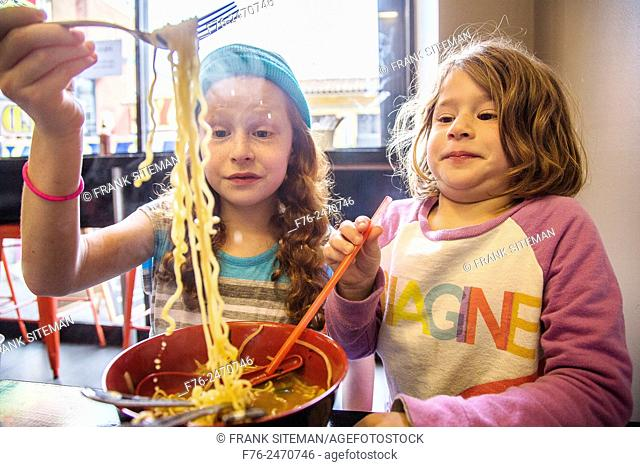 10 year old girl with woolen cap on and her 6 year old sister, eating noodles in a noodle restaurant in Berkeley, CA