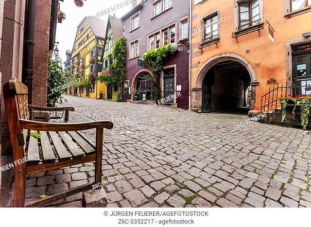 lane of the tourist destination Riquewihr, village of the Alsace Wine Route, France, cobblestone alley with vine and flower decoration