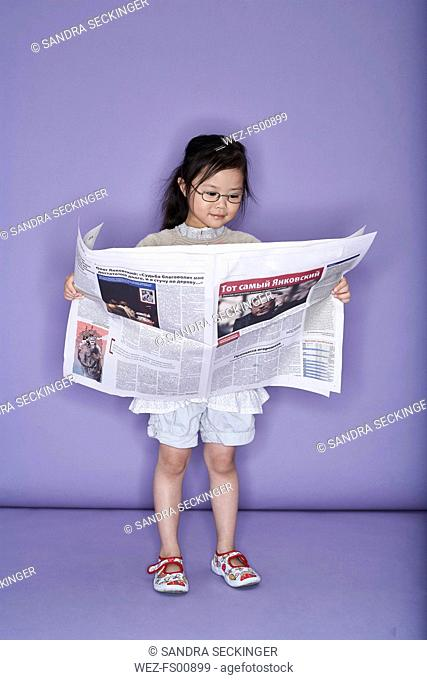 Portrait of little girl with newspaper