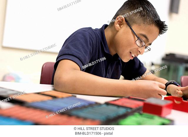 Hispanic student coloring with pastels at desk in classroom