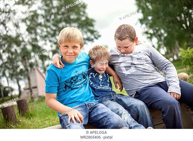 Happy friends sitting on wood at schoolyard