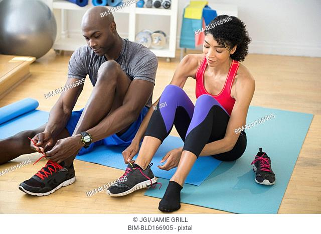 Couple tying sneakers in gym