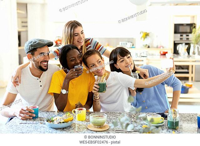 Friends with drinks taking a selfie in kitchen