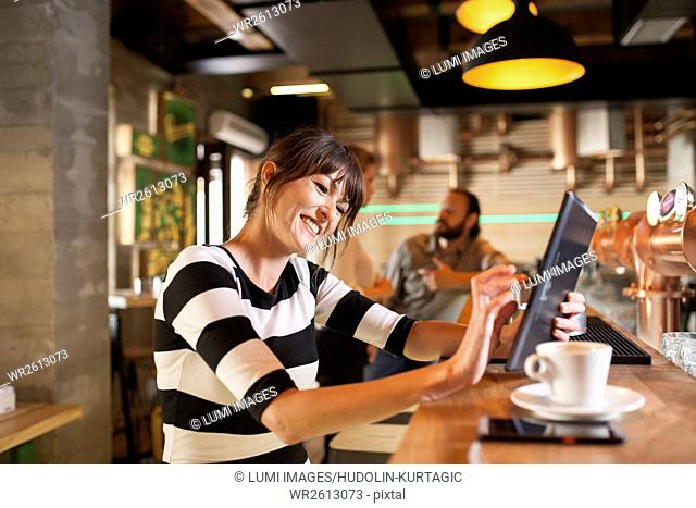 Woman in coffee shop using digital tablet