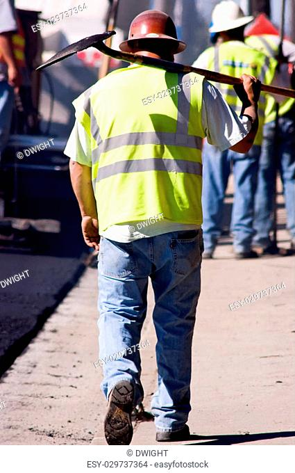 A tired paving worker walking down the street, carrying a shovel