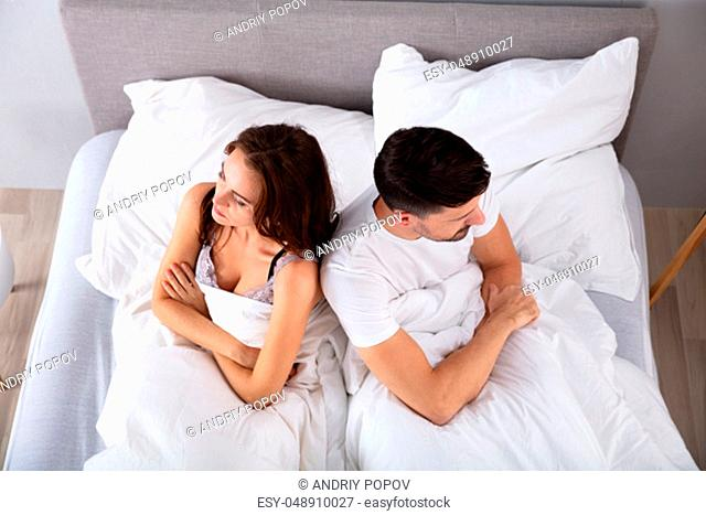 Top View Of Despaired Married Couple Back To Back On Bed