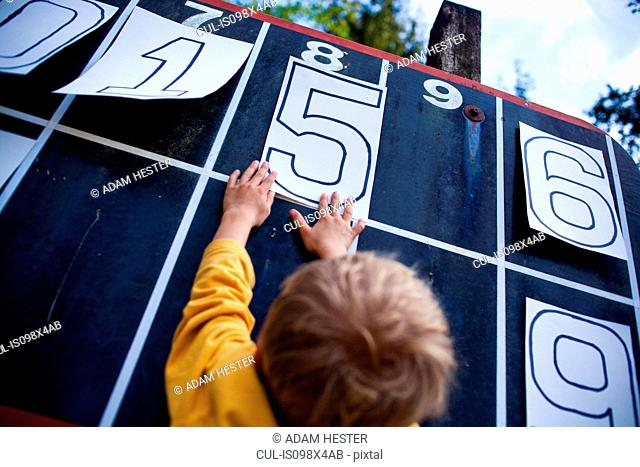 Young boy playing with numbers on scoreboard