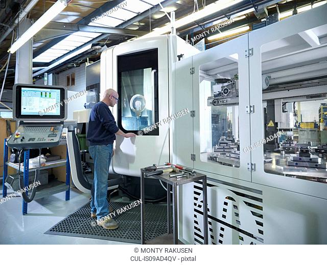 Engineer at computer numerical controlled lathe (CNC) in factory