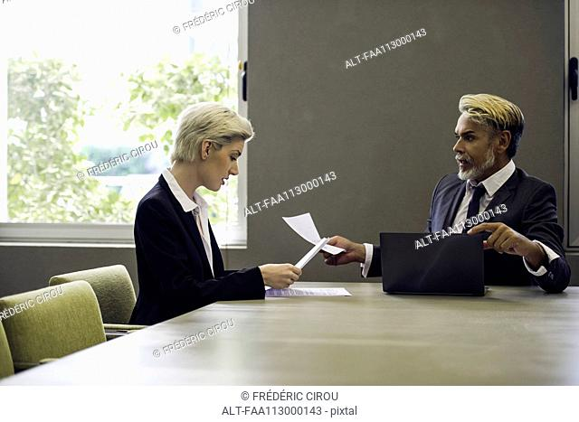 Woman and man in office reading document