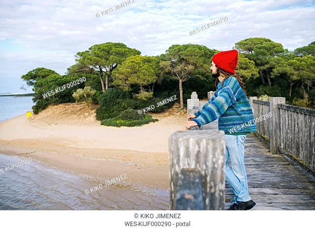 Young man with dreadlocks and wool cap on wooden bridge by the sea