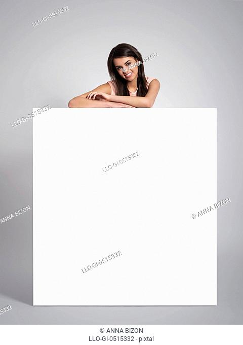 Smiling beautiful woman leaning on empty whiteboard. Debica, Poland