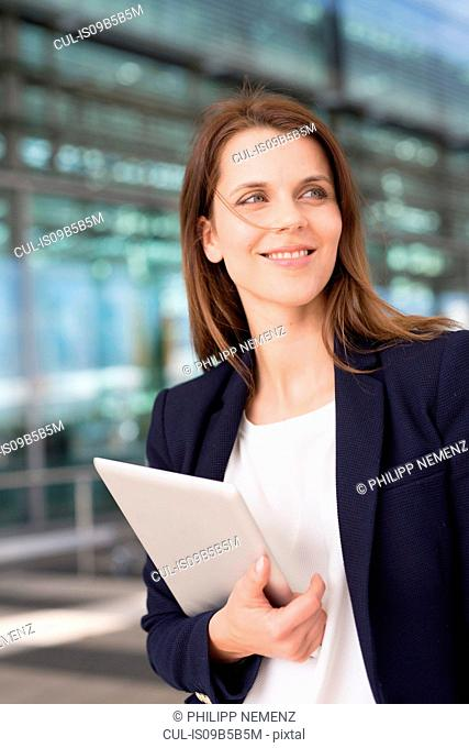 Businesswoman holding digital tablet outside airport