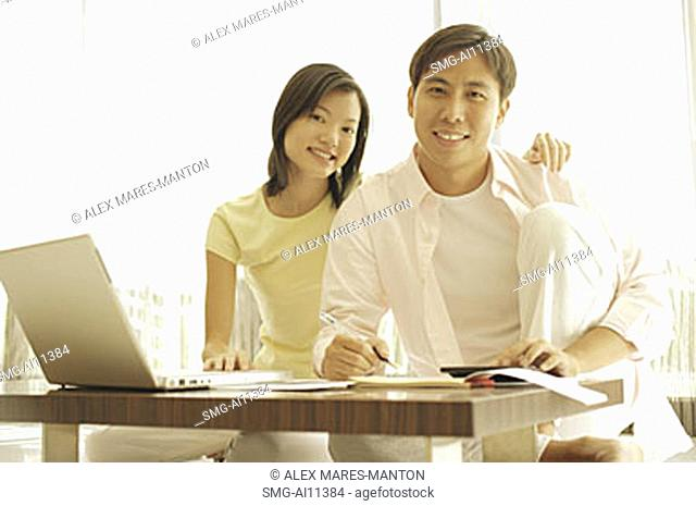 Couple sitting side by side at home, laptop open in front of them