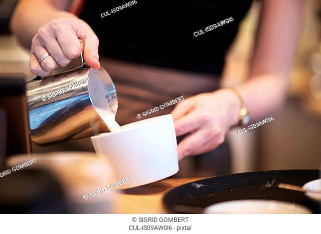Cropped shot of waitress pouring milk into coffee cup in cafe