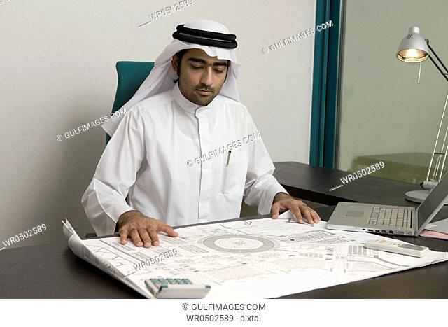 Arab businessman looking on a blueprint, sitting at the office