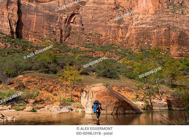 Climber crossing river, Zion National Park, Utah, USA
