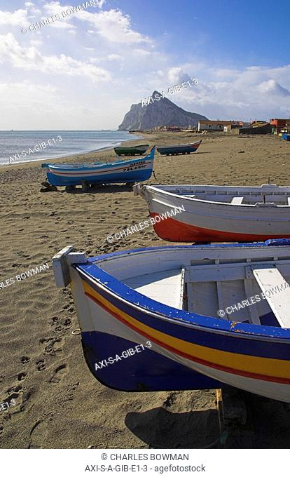 Painted fishing boats on beach and Rock of Gibraltar