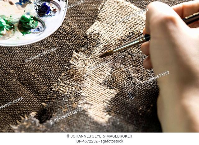 Restoration studio, restorer, hand patinates the woven in patch of linen with brush and paint, Munich, Bavaria, Germany