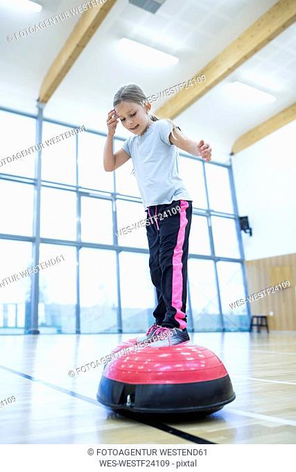 Schoolgirl balancing on exercise equipment in gym class
