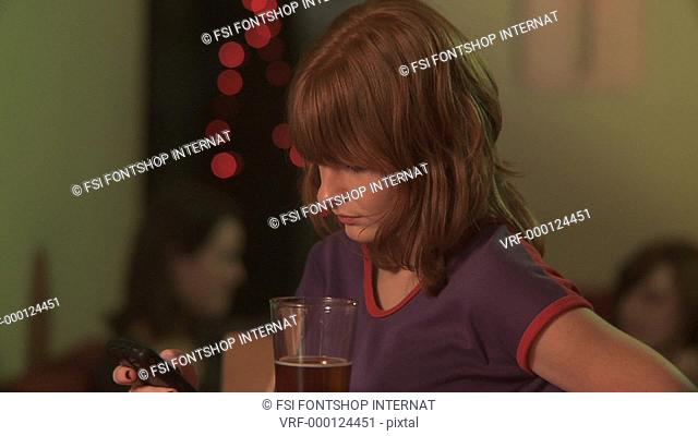 MS, Selective Focus, A woman at a bar using a mobile phone when a man approaches her