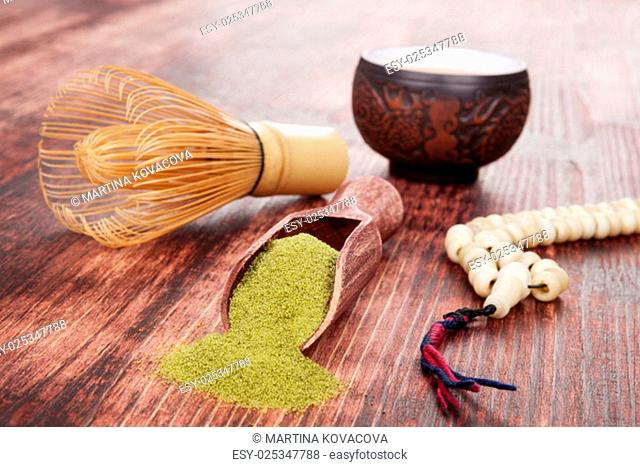 Traditional tea ceremony. Powdered green tea matcha, hot tea in ceramic cup, bamboo chasen and buddhist necklace on brown wooden background