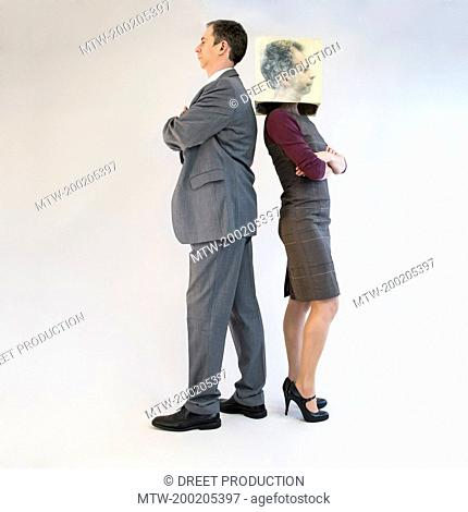 Businessman standing back to back of businesswoman wearing mask