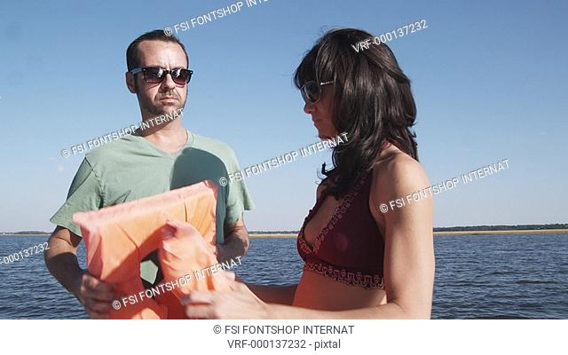 MS, Lockdown of a couple on a boat helping each other put on life jackets