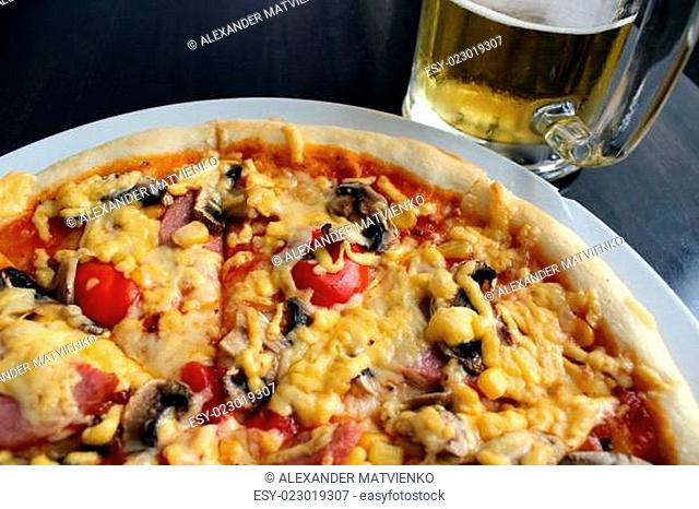 very tasty pizza with glass of beer