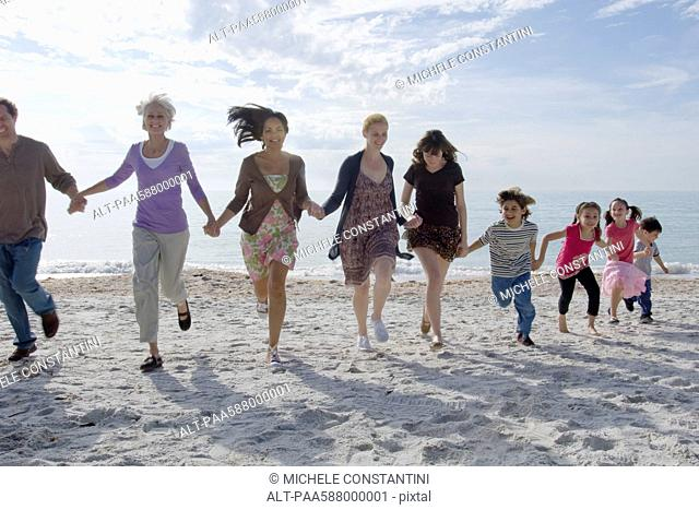 Group of people holding hands and running on beach