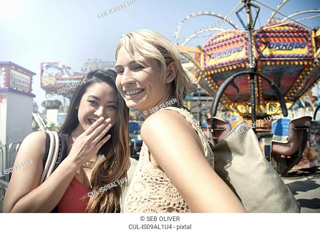 Two women at fairground, laughing and watching surroundings