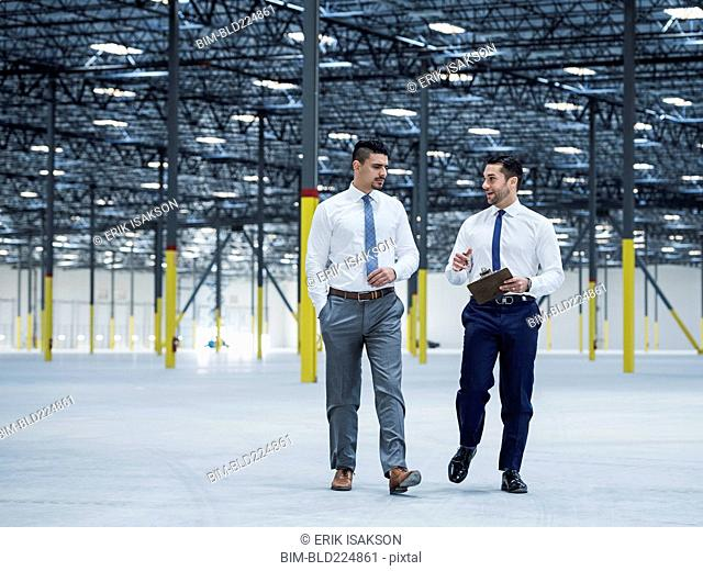 Businessmen with clipboard talking in empty warehouse