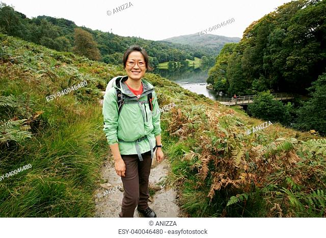 Smiling East Asian Woman hiking in Lake District, Cumbria, UK. Grasmere lake in the back ground