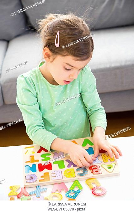 Little girl learning alphabet with wooden letters at home