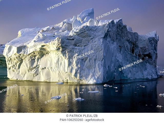 25.06.2018, Gronland, Denmark: Icebergs drifting in the sea in front of the coastal town of Ilulissat in western Greenland in the late evening to the late...