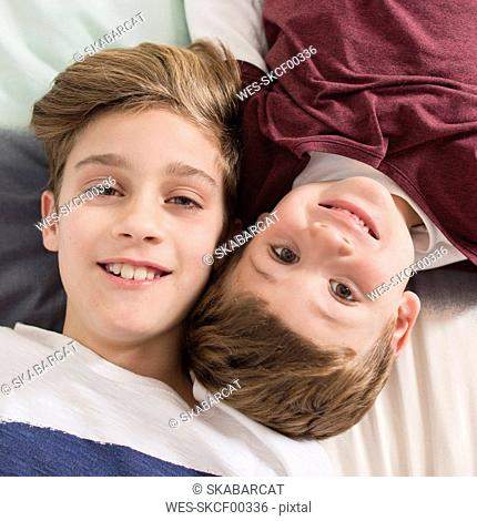 Top view of two smiling brothers lying on bed