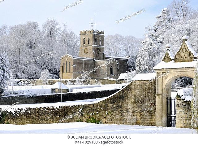 Oxfordshire Church in sunshine and freshly fallen snow with a gentle blue sky behind  Gateway in front  Snow covered trees